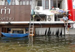 Thailand floods: A Thai resident waits for help on a flood submerged building