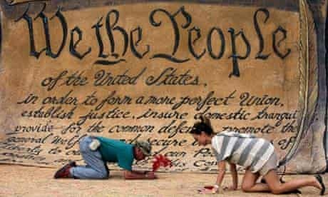 People sign a huge copy of the US constitution at the Occupy DC camp in Washington