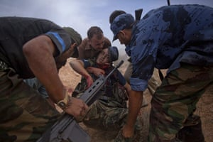 From the agencies: Manu Brabo: A wounded NTC fighter is careried away by comrades
