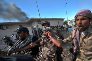 Sirte street battles: NTC fighters evacuate a wounded comrade after he was shot by a sniper