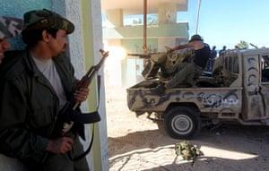Sirte street battles: An NTC fighter watches comrades fire their gun