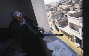 Sirte street battles: A revolutionary fighter fires his machine gun towards loyalist positions
