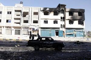 Sirte street battles: An anti-Gaddafi fighter fires a heavy machine gun during clashes