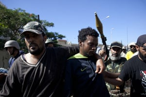 Sirte street battles: An alleged member of the pro-Gaddafi forces is captured during a battle