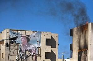 Sirte street battles: A tattered banner depicting Muammar Gaddafi hangs from a building