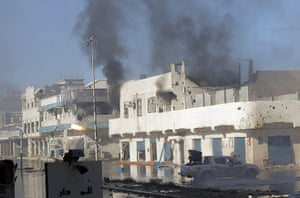Sirte street battles: Anti-Gaddafi fighters fire a rocket during clashes on the frontline