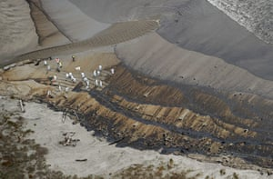Rena oild spill: New Zealand army soldiers  clear the oil from Papamoa Beach, New Zealand