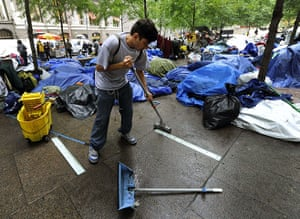 Occupy Wall Street: A protester sweeps the pavement
