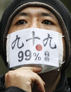 Occupy Global: An Occupy Tokyo protester wears a mask during a rally in Tokyo
