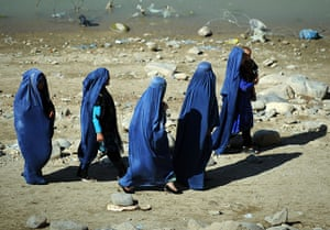 24 Hours: A group of burqa-clad Afghan women walk along the shore near Kabul