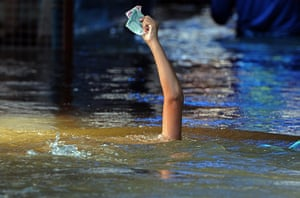 24 Hours: A Thai boy holds aloft banknotes to keep them dry