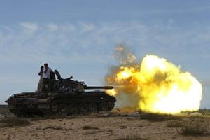 Sirte: Anti-Gaddafi fighters fire from a tank towards pro-Gaddafi forces in Sirte