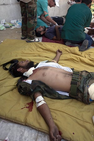 Sirte: Wounded NTC fighters receive treatment near the front line in Sirte