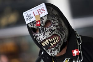 Global Occupy: A protester wears a mask with the logo of UBS in Zurich