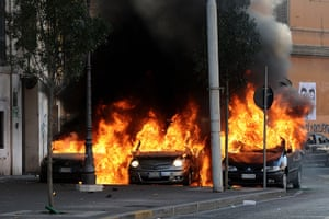 Global Occupy: Cars burn during the Occupy demonstration in Rome