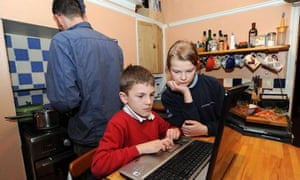 A father cooks the tea in the kitchen while his children use the laptop for homework