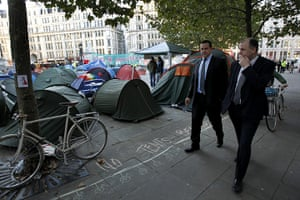 Occupy London: businessmen walk past tents