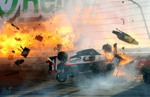 Dan Wheldon Retrospective: Race car of driver Power hits the wall as flames from Wheldon's car burst