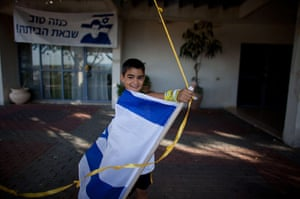 Shalit release: An Israeli boy plays with a flag near the house of Gilad Shalit