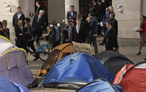 Occupy London: Business people look at tents at Occupy London Stock Exchange