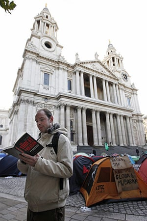 Occupy London: A man reads a book near protesters' tents outside St Paul's Cathedral