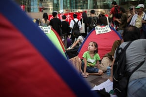 Occupy World Protests: A girl sits among tents outside the Hong Kong stock exchange