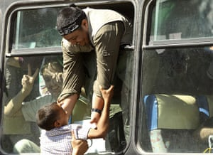 Shalit release: A freed Palestinian a lifts a boy at the Rafah crossing border
