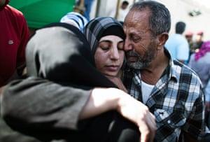 Shalit release: A Palestinian prisoner hugs relatives after arriving in Mukata