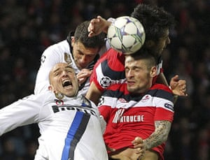 Tuesday Champions League: Lille's Debuchy jumps for the ball with Inter Milan's Cambiasso and Motta