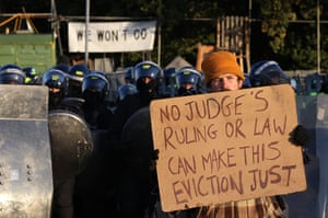 Dale Farm camp: An activist holds up a placard in front of a police line, Dale Farm