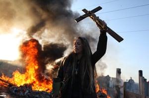 Dale Farm camp: An activist holds up a crucifix as a barricade burns, Dale Farm