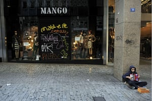 Greece strikes & protests: A boy plays accordion in front of a closed shop in an Athens shopping area