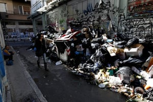 Greece strikes & protests: A woman passes a pile of rotting rubbish in a narrow street in Athens