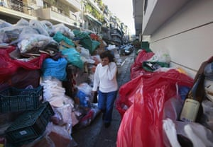 Greece strikes & protests: A woman covers her nose as she walks by a wall of piled-up rubbish