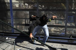 Greece strikes & protests: A riot policeman catches a protester who attacked a steel barricade