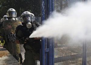 Greece strikes & protests: A riot policeman sprays tear gas at demonstrators