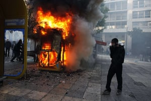 Greece strikes & protests: A protester wearing a gas mask stands next to a fire