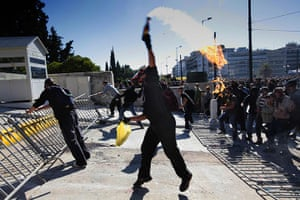 Greece strikes & protests: A masked youth throws a petrol bomb at police during riots