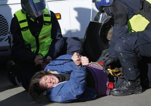 Dale Farm: Police officers arrest an activist as they clear a tower