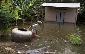 Cambodia floods: A man pulls a giant jar in flood waters on a street in Kandal province