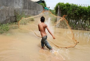 Cambodia floods: A boy casts a fishing net into flood waters on a street in Kandal