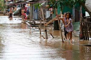 Cambodia floods: Children walk through flood waters on a submerged makeshift wooden walkway