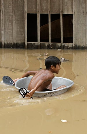 Cambodia floods: A boy uses an aluminum pot at flooded Croy Changvar village in Phnom Penh