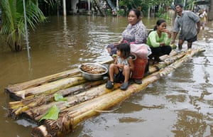 Cambodia floods: Cambodian villagers on a makeshift raft travel though a flooded street
