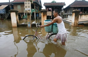 Cambodia floods: A Cambodian man walks with his bicycle though a flooded street