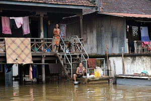 Cambodia floods: Cambodians wash pots in floodwaters at Kian Svay district