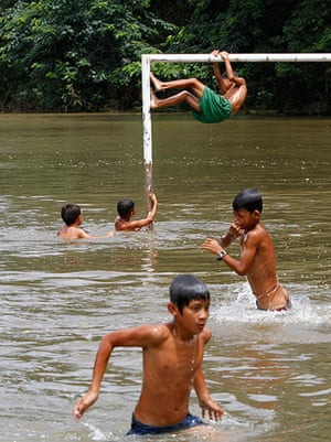 Cambodia floods: Children play in flood waters on a goal post in Kandal