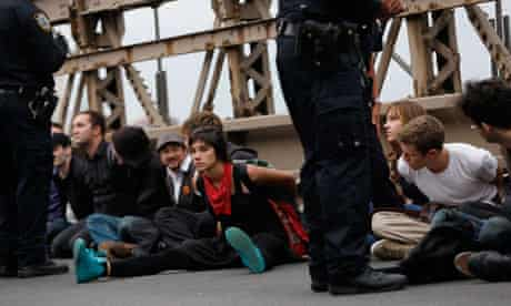 Protesters sit in plastic handcuffs on the Brooklyn Bridge during an Occupy Wall Street march