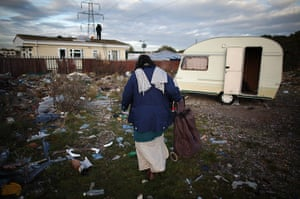 Dale Farm: a woman makes her way past an abandoned caravan