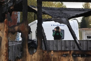 Dale Farm evictions: A traveller looks through the remains of a burnt building